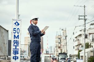 手元を見ている作業服とヘルメットの男性の写真素材 [FYI01465267]