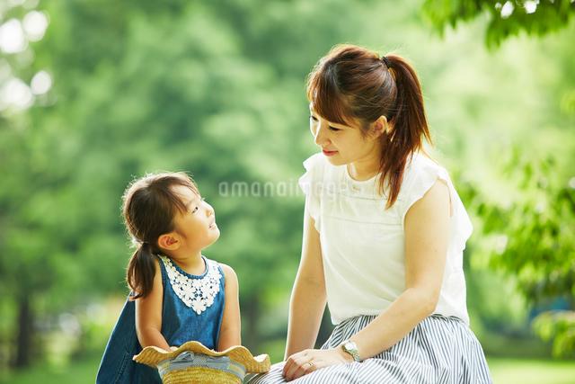 公園内で座って話をするお母さんと女の子の写真素材 [FYI01465294]