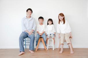 白壁の前で椅子に座る4人家族の写真素材 [FYI01465303]