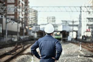 線路に立つ作業服とヘルメットの男性の写真素材 [FYI01465313]