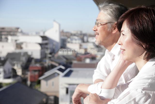ベランダから街並みを眺めるミドル夫婦の写真素材 [FYI01465336]