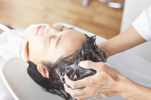 シャンプー台で髪を洗ってもらっている女性の写真素材 [FYI01465346]
