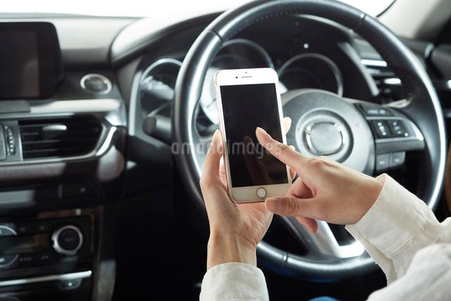 運転席でスマートフォンを操作する女性の写真素材 [FYI01465352]