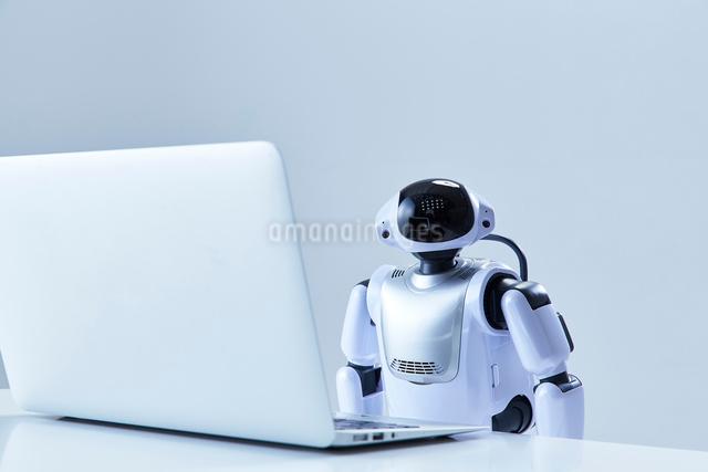 ノートパソコンを操作するミニロボットの写真素材 [FYI01465382]