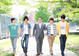 教授を囲み歩く4人の大学生の写真素材 [FYI01465435]