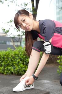 靴紐を直すジョギング姿の若い女性の写真素材 [FYI01465440]