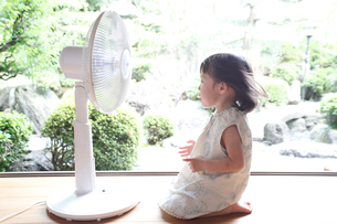 縁側で扇風機にて涼む女の子の写真素材 [FYI01465447]