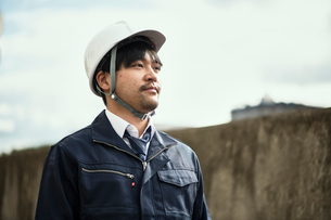 遠くを見ている作業服とヘルメットの男性の写真素材 [FYI01465457]