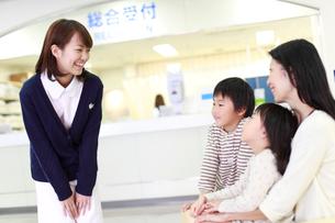 来院者に微笑みかける女性職員の写真素材 [FYI01465460]