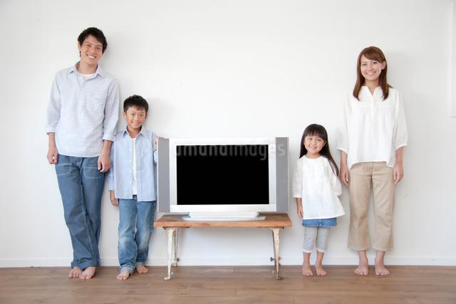 テレビを囲む4人家族の写真素材 [FYI01465469]
