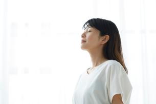 明るい窓際で目を閉じて立つ笑顔の女性の写真素材 [FYI01465488]