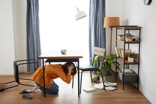 自宅にいるときに地震がきて怯える女性の写真素材 [FYI01465507]