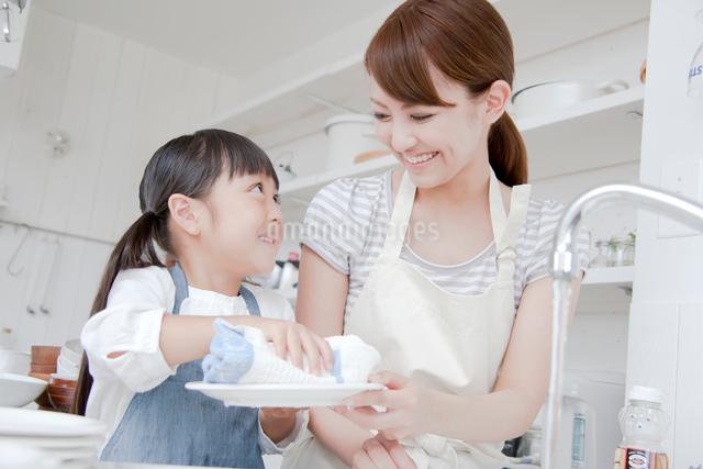 キッチンで洗い物を手伝う女の子と母親の写真素材 [FYI01465522]