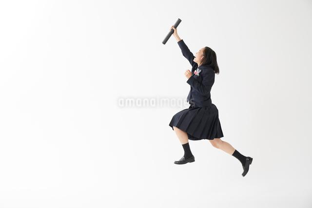 卒業証書の筒を持ってジャンプする女子高生の写真素材 [FYI01465545]