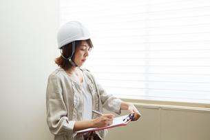 窓辺でヘルメットを被り書類とペンを持つ女性の写真素材 [FYI01465588]