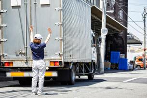大きなトラックを誘導する働く女性の写真素材 [FYI01465598]