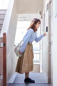 マンションのドア前でインターフォンをならす女性の写真素材 [FYI01465603]