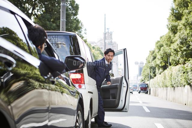 車から降りてくる男性と窓から顔を出す男性の写真素材 [FYI01465616]