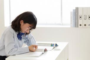 白い机で勉強をする女子高生の写真素材 [FYI01465640]