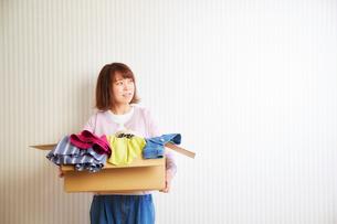 段ボール箱に入った服を運ぶ女性の写真素材 [FYI01465659]