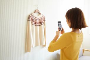 ハンガーに掛かったセーターを撮影する女性の写真素材 [FYI01465677]