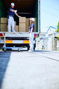 トラックの荷台に載っている男性と前に立つ女性の写真素材 [FYI01465715]