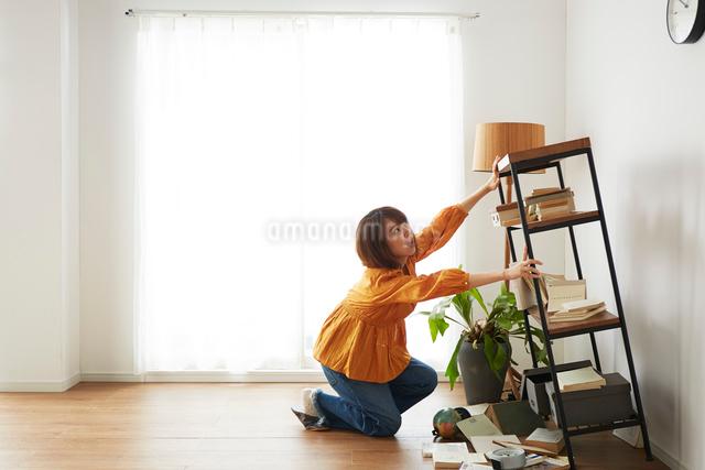地震で倒れてきた本棚を支える女性の写真素材 [FYI01465717]