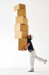 白バックの空間でたくさん重なったダンボールを運ぶ作業着の男性の写真素材 [FYI01465817]