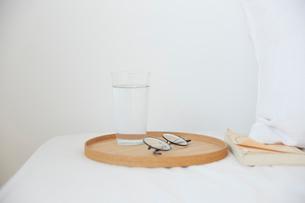 ベッドの枕元に置かれたグラスの水とメガネと文庫本の写真素材 [FYI01465852]