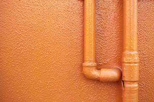 オレンジのエンボス壁とパイプの写真素材 [FYI01465880]