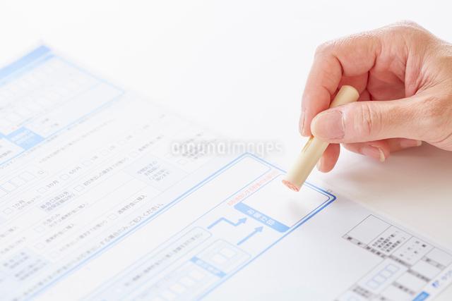 書類と印鑑を持つ女性の手元の写真素材 [FYI01465917]