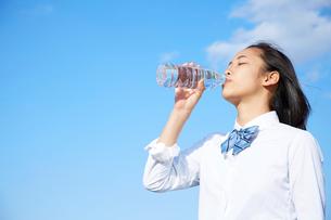 青空の下でペットボトルの水を飲む女子高生の写真素材 [FYI01465993]