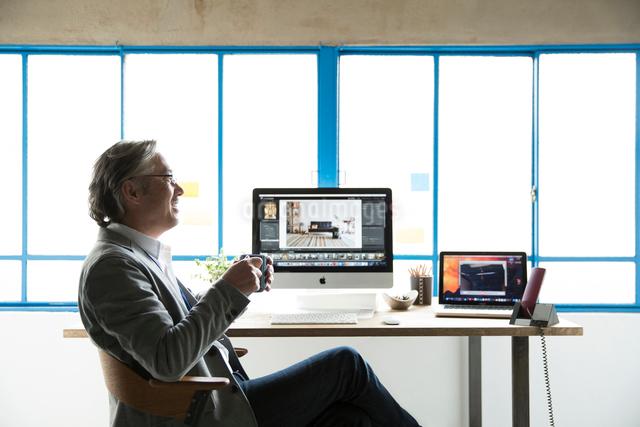 デスクでマグカップを持つ横向きのシニアビジネスマンの写真素材 [FYI01466000]