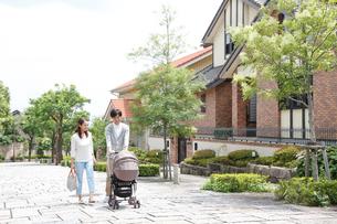 新緑の住宅街でベビーカーを押す若いカップルの写真素材 [FYI01466013]