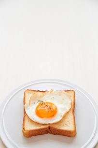 白い皿の上に置かれた食パンと目玉焼きの写真素材 [FYI01466095]