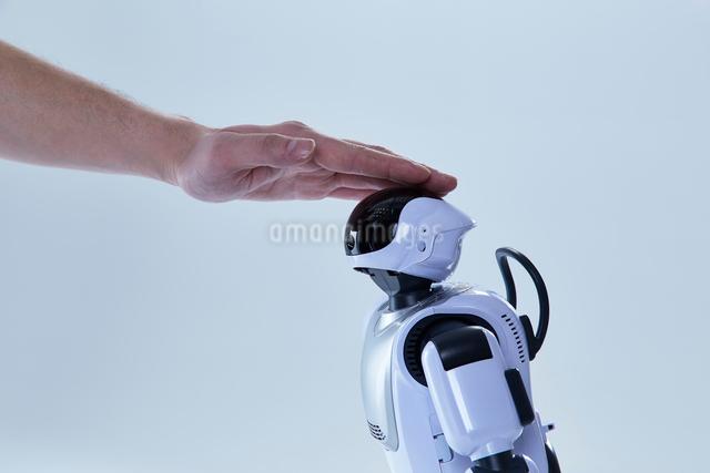 ロボットの頭を撫でる人間の手の写真素材 [FYI01466116]