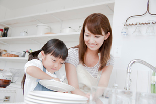 キッチンで洗い物を手伝う女の子と母親の写真素材 [FYI01466160]