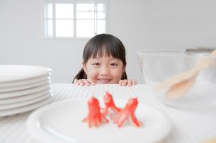 蛸ウィンナーを見て微笑む女の子の写真素材 [FYI01466172]
