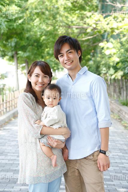 新緑の道で微笑む若い3人家族の写真素材 [FYI01466199]