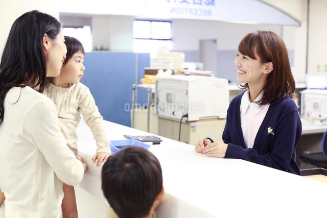 病院の受付で来院者れに対応する女性職員の写真素材 [FYI01466210]