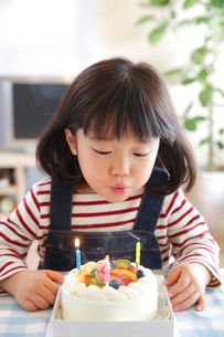 バースデイケーキのろうそくを吹き消す女の子の写真素材 [FYI01466212]