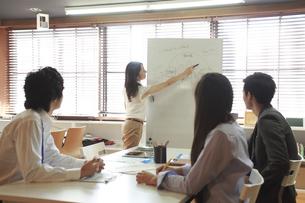 シェアオフィスでミーティングをする私服の男女ビジネスマン4人の写真素材 [FYI01466217]