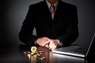 パソコンでビットコインのビジネスをするスーツを着た男性の写真素材 [FYI01466227]