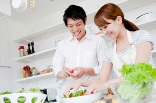 キッチンで料理をするカップルの写真素材 [FYI01466244]