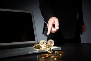 ビットコインとパソコンと指をさすスーツを着た男性の写真素材 [FYI01466470]