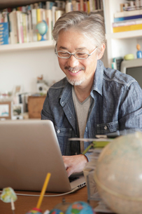 書斎でノートパソコンを見るミドル男性の写真素材 [FYI01466537]