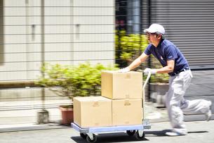台車を使って段ボールを運んでいる男性の写真素材 [FYI01466876]