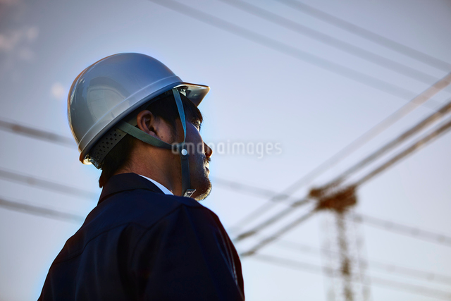遠くを見ている作業服とヘルメットの男性の写真素材 [FYI01466981]