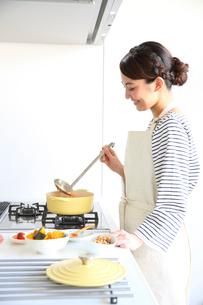 キッチンで料理をする若い女性の写真素材 [FYI01467050]