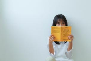 床に座って読書する少女の写真素材 [FYI01467093]